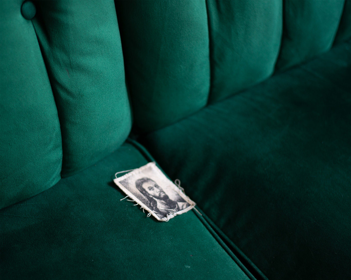 Small fabric print of a drawing depicting Black Jesus placed on the cushion of a green velvet couch