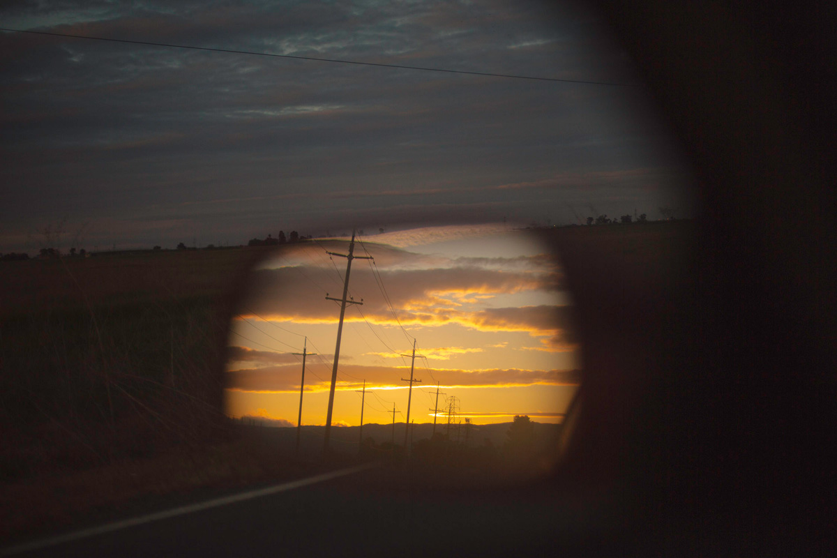 Abstracted car-mirror reflection of golden sunset with long clouds and power lines, against darkening sky over fields