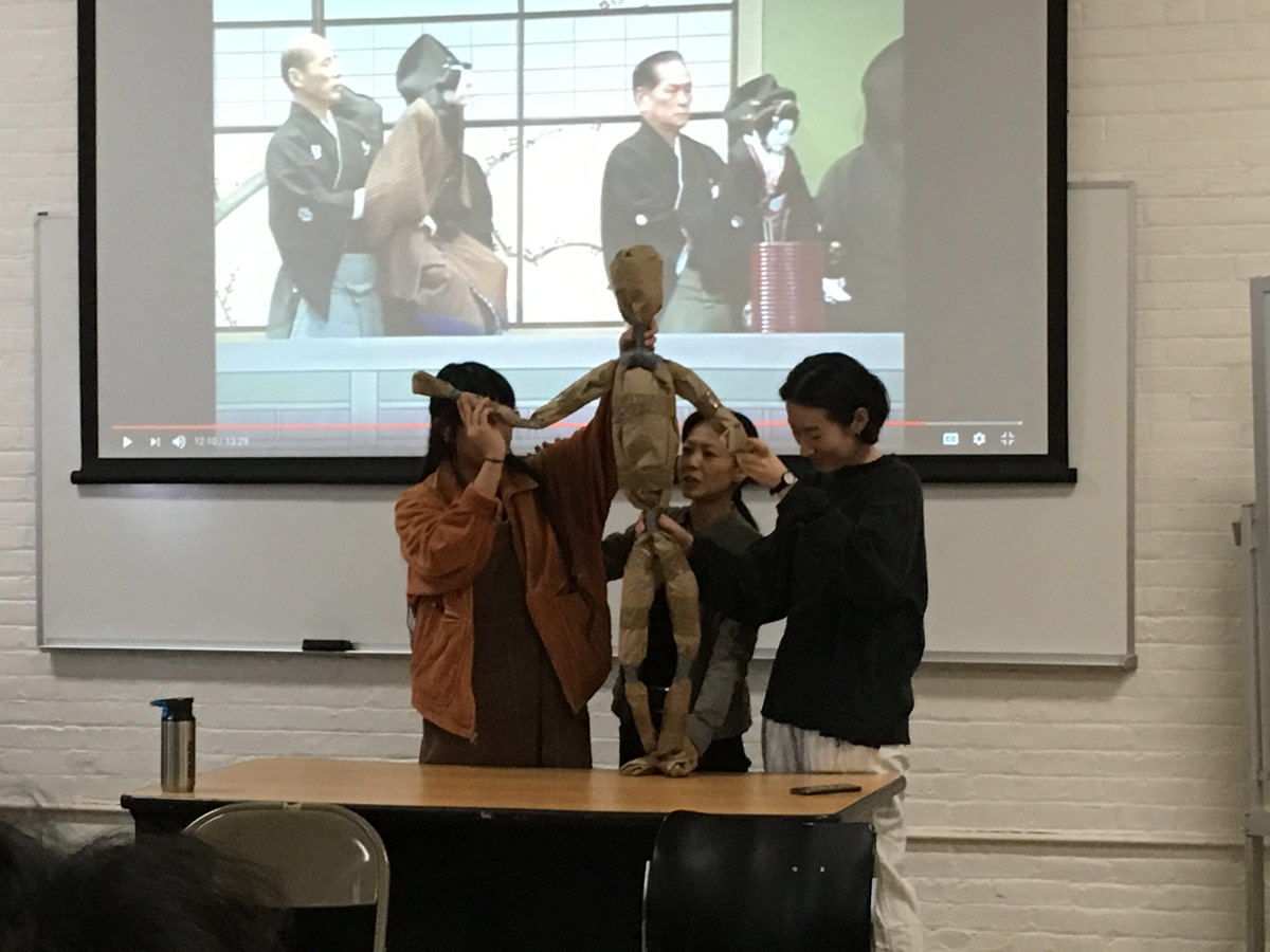 Three people hold up a puppet during a demonstration in front of a class