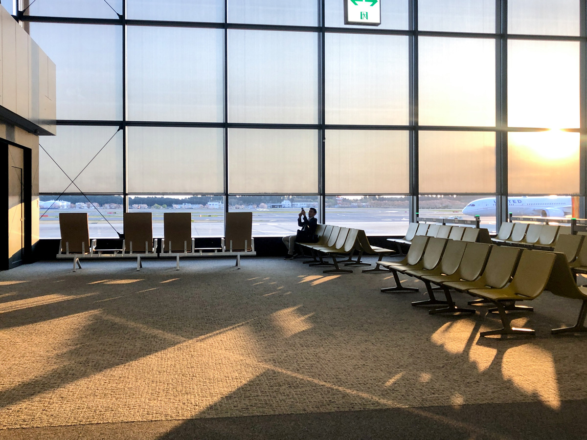 Near-empty airport waiting area with sun low on horizon casting long shadows through wall of windows