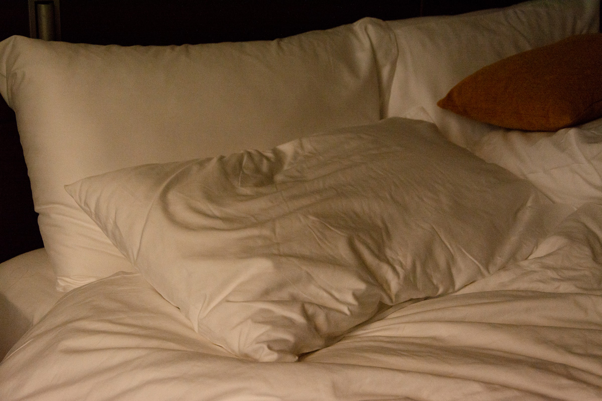 Rumpled pillow sits atop quarantine hotel bed