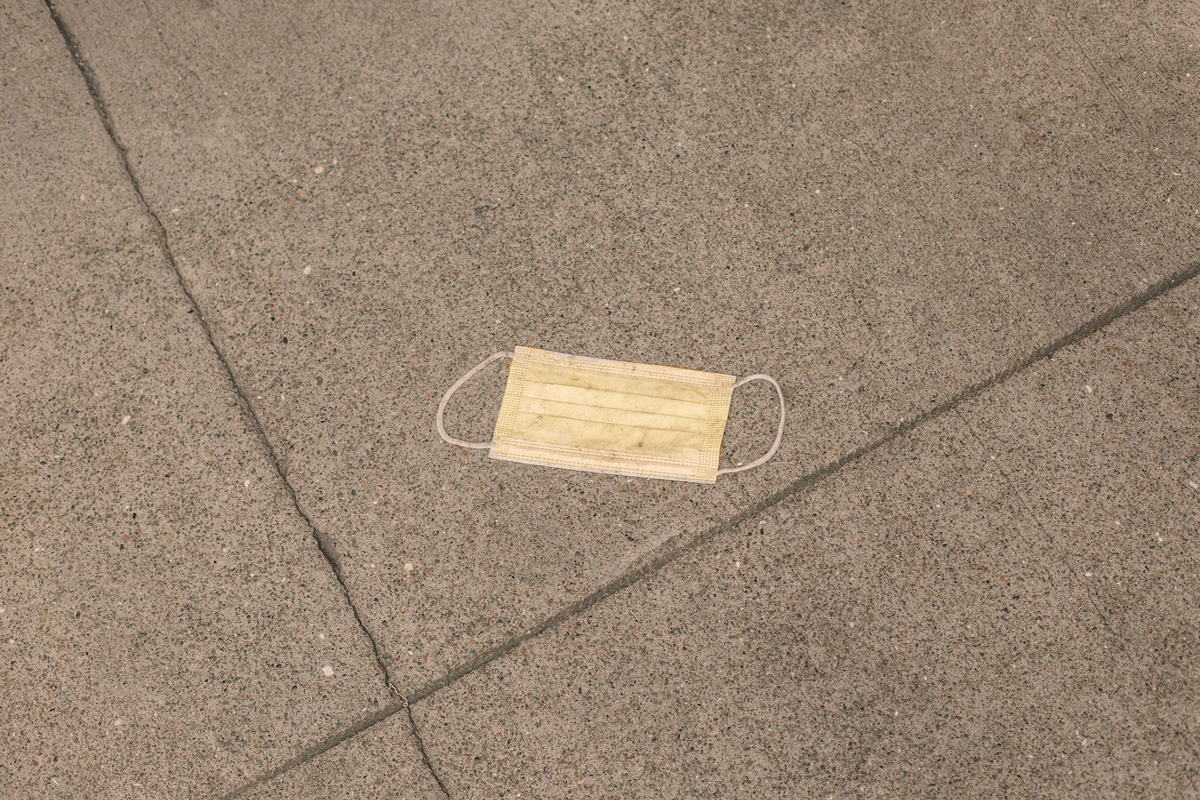 Light yellow discarded surgical mask flattened on pavement