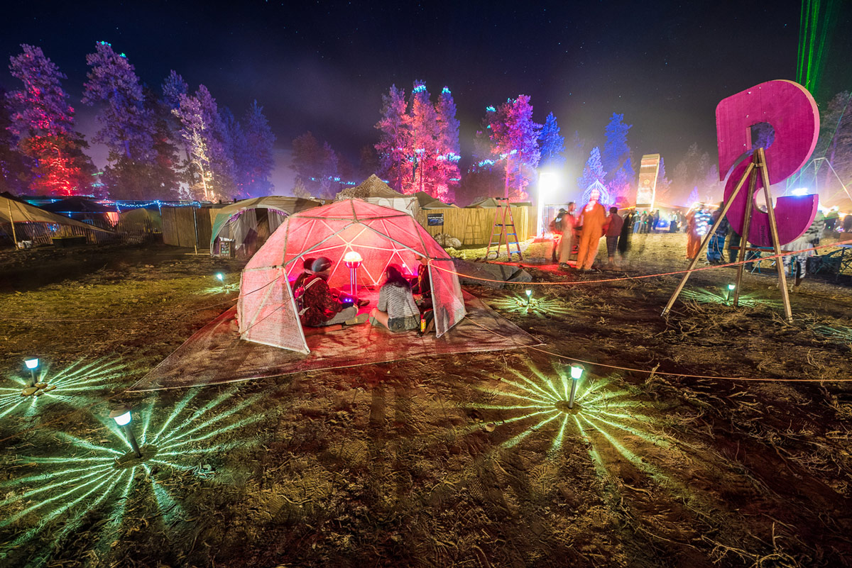 People sitting in a colorful, small dome within festival grounds that are lit up at night.